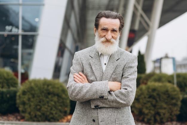 Retrato de hombre senior feliz con barba gris en los edificios de oficinas con espacio de copia