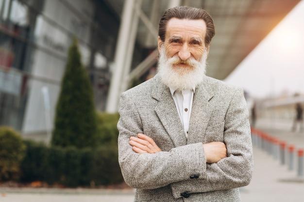 Retrato de hombre senior feliz posando en los edificios de oficinas