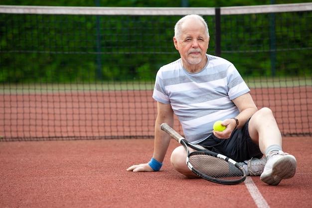 Retrato de hombre senior jugando al tenis en un exterior, deportes jubilados