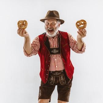 Retrato de hombre senior de oktoberfest con sombrero, vistiendo la ropa tradicional bávara, sosteniendo pretzels