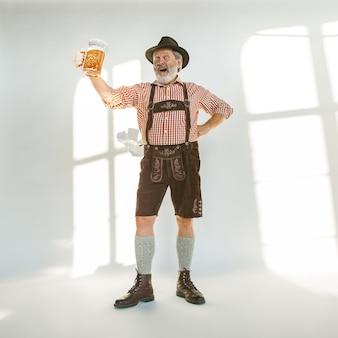 Retrato de hombre senior de oktoberfest con sombrero, vistiendo la ropa tradicional bávara. tiro de cuerpo entero masculino en estudio sobre fondo blanco. la celebración, vacaciones, concepto de festival. beber cerveza.
