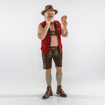Retrato de hombre senior de oktoberfest con sombrero, vistiendo la ropa tradicional bávara. tiro de cuerpo entero masculino en estudio sobre fondo blanco. la celebración, vacaciones, concepto de festival. comiendo bocanada.