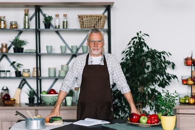 Retrato de hombre senior de pie detrás de la mesa en la cocina
