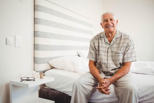 Retrato de hombre senior sentado en la cama y sonriendo en el dormitorio