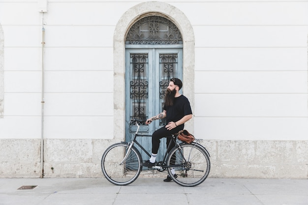 Retrato de un hombre sentado en bicicleta frente a la puerta azul