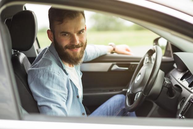 Retrato de hombre sentado en el coche