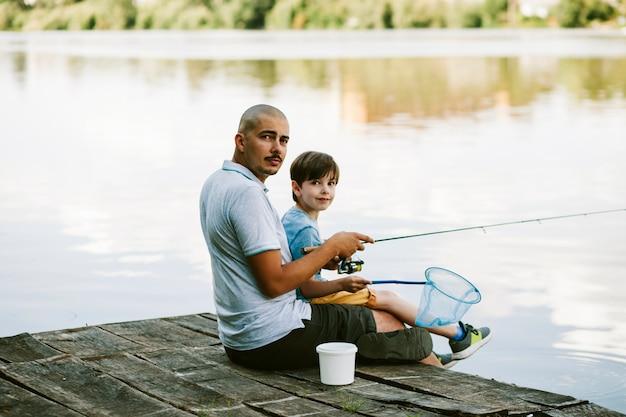 Retrato de un hombre sentado en el muelle con su hijo pescando en el lago