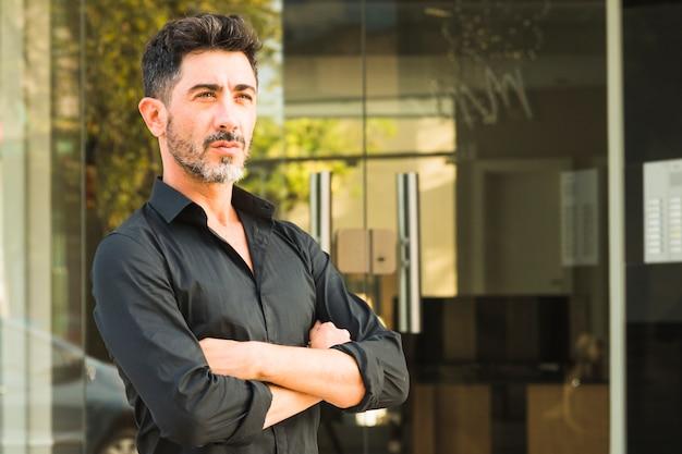 Retrato de hombre serio en camisa negra de pie frente a puerta cerrada