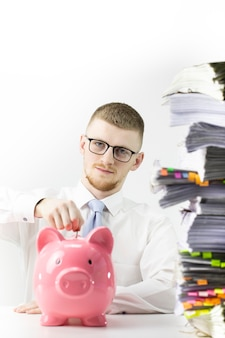 Retrato de hombre serio insertando monedas en piggybank en la oficina, contador inteligente