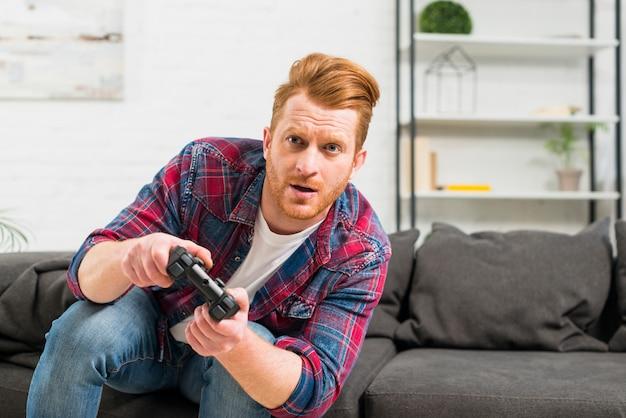 Retrato de un hombre serio jugando al videojuego con joystick en casa