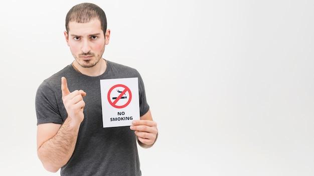 Retrato de un hombre serio que lleva a cabo la muestra de no fumadores que señala el dedo hacia la cámara