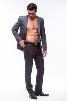 Retrato de un hombre sexy guapo con una chaqueta y con un torso desnudo aislado en una pared blanca