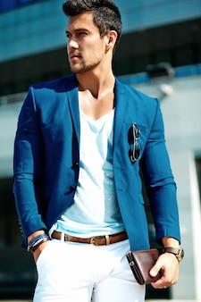 Retrato de hombre sexy modelo masculino guapo vestido con elegante traje posando en el fondo de la calle