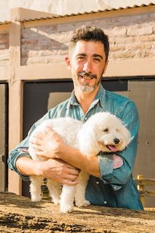 Retrato de un hombre sonriente abrazando a su perro blanco