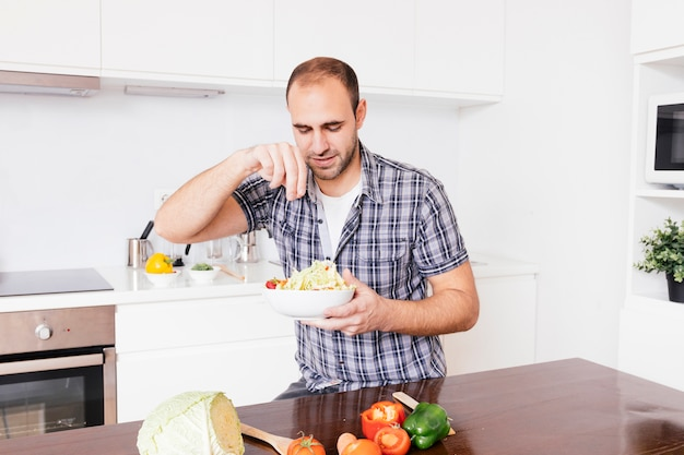 Retrato de un hombre sonriente agregando especias en ensalada