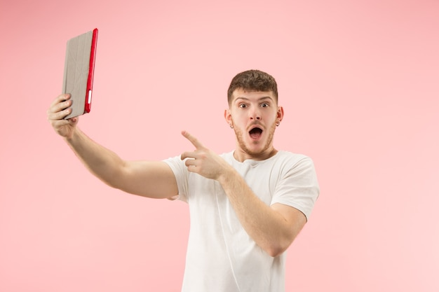 Retrato de hombre sonriente apuntando a la computadora portátil con pantalla en blanco aislada sobre fondo rosa studio. las emociones humanas, el concepto de expresión facial y el concepto de publicidad.