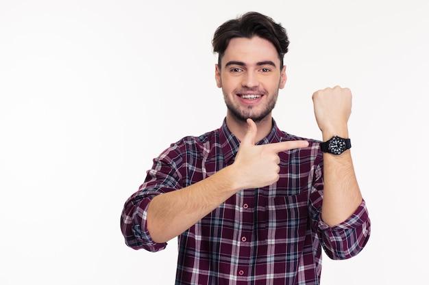 Retrato de un hombre sonriente apuntando con el dedo en el reloj de pulsera aislado en una pared blanca