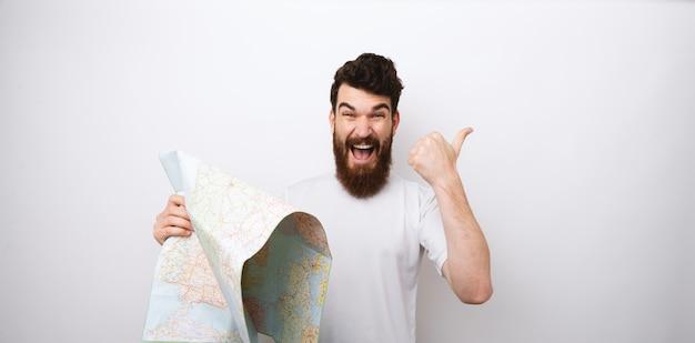 Retrato de hombre sonriente con barba sosteniendo mapa y mostrando los pulgares para arriba, listo para viajar, concepto de vacaciones