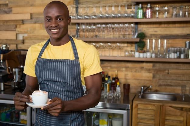 Retrato de hombre sonriente barista sosteniendo la taza de café en el café