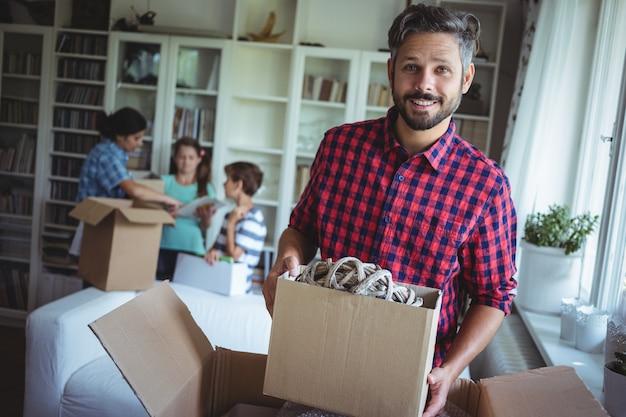 Retrato de hombre sonriente con cajas de acarton mientras la familia de pie en el fondo