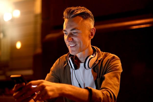 Retrato de hombre sonriente en la ciudad por la noche con auriculares y smartphone
