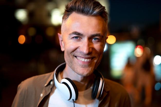 Retrato de hombre sonriente en la ciudad por la noche con auriculares