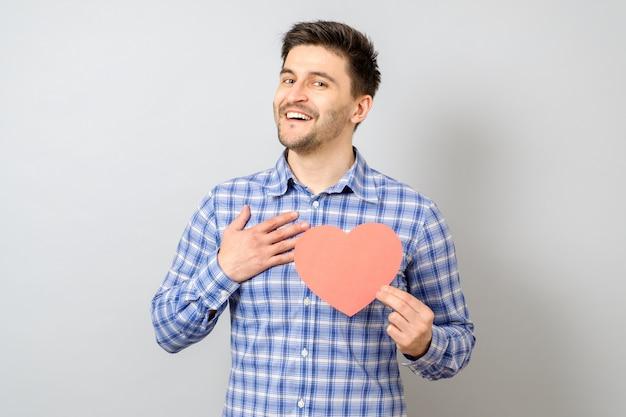 Retrato de hombre sonriente con corazón de papel rojo