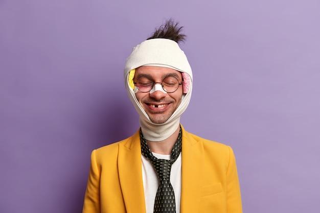 Retrato de hombre sonriente divertido al que le faltan dientes después de un trauma grave, se para con los ojos cerrados, piel magullada, cabeza vendada, se cayó durante la bicicleta, tiene un período de recuperación, aislado en una pared púrpura