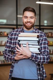 Retrato de un hombre sonriente estudiante sosteniendo libros en la biblioteca