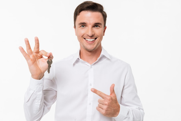 Retrato de un hombre sonriente feliz en camisa con llaves