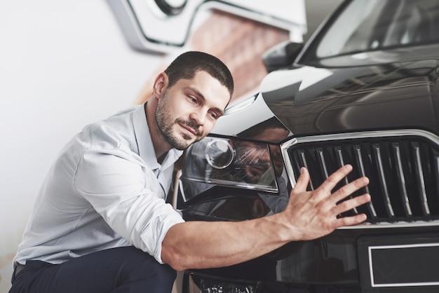 Retrato de un hombre sonriente feliz que elige un coche nuevo en la cabina.