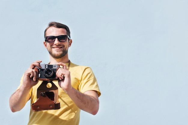 Retrato de hombre sonriente con gafas de sol tomando foto con cámara retro