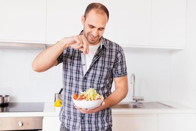 Retrato de un hombre sonriente que sazona la sal en la ensalada en la cocina