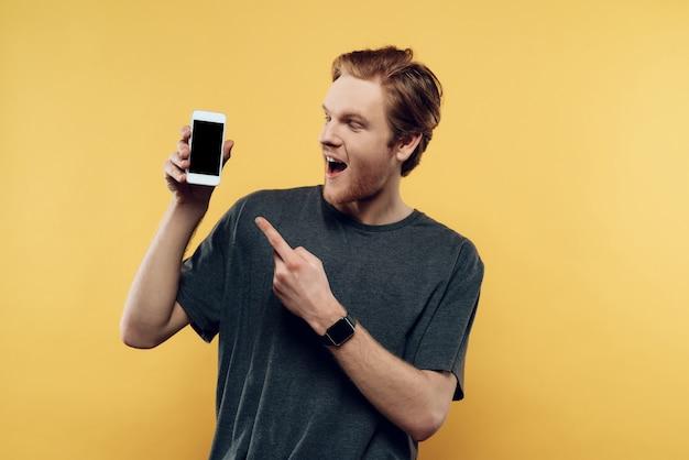 Retrato del hombre sonriente que sostiene smartphone