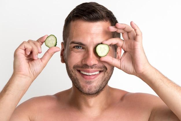Retrato de hombre sonriente sosteniendo y ocultando los ojos con una rodaja de pepino