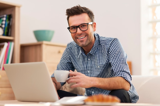 Retrato de hombre sonriente trabajando en casa