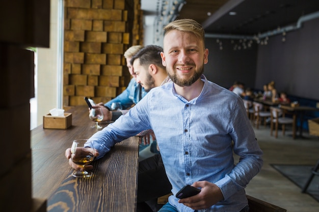 Retrato de hombre sonriente con vaso de bebida en el bar
