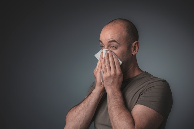 Retrato de un hombre soplando su nariz con un pañuelo