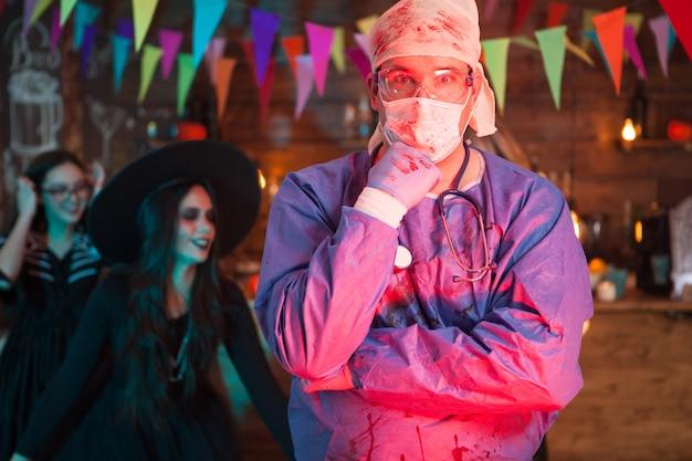 Retrato de hombre sorprendido disfrazado de médico para la celebración de halloween. bruja aterradora en el fondo.