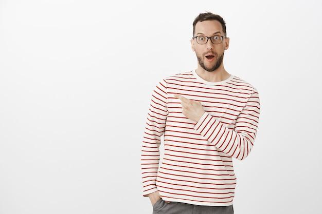 Retrato de hombre sorprendido sonriendo con gafas, diciendo wow y apuntando a la esquina superior izquierda