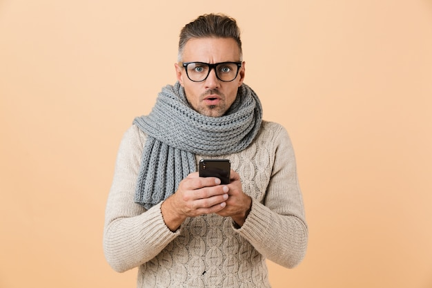 Retrato de un hombre sorprendido vestido con suéter y bufanda que se encuentran aisladas sobre la pared beige, mediante teléfono móvil