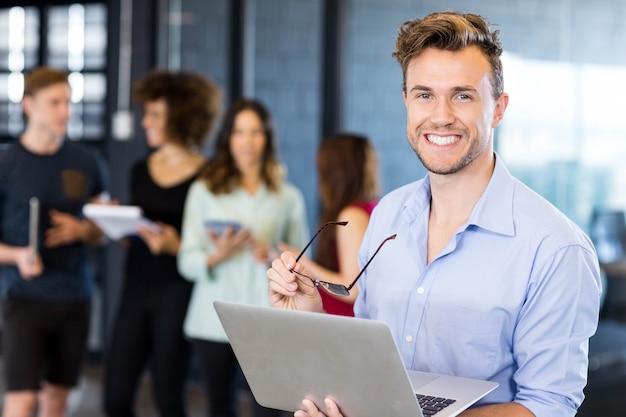 Retrato de hombre sosteniendo una computadora portátil y sonriendo mientras colegas de pie detrás de la oficina