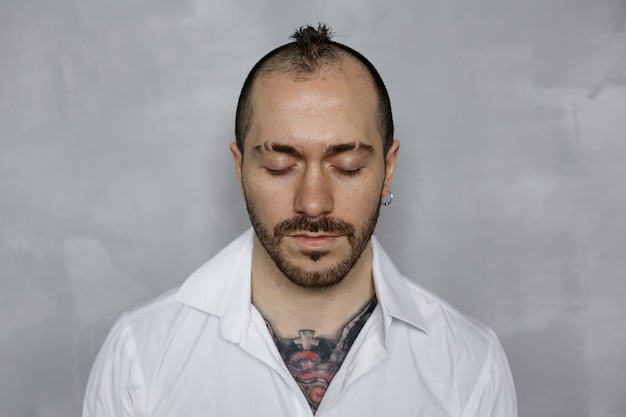 Retrato de hombre tatuado con barba en camisa blanca con los ojos cerrados
