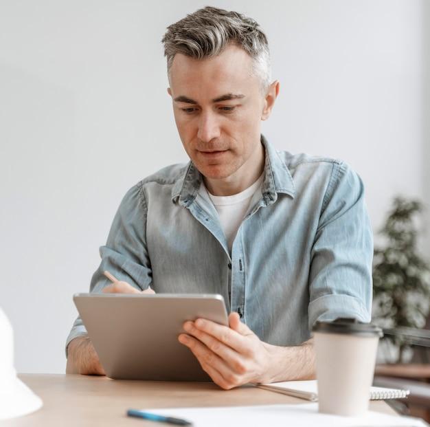Retrato de hombre trabajando en tableta
