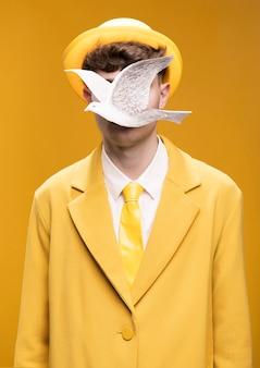 Retrato de hombre en traje amarillo con paloma plateada enfrente de la cara