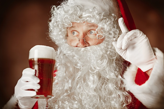 Retrato de hombre en traje de santa claus - con una lujosa barba blanca, sombrero de santa y un traje rojo en el fondo rojo del estudio con cerveza
