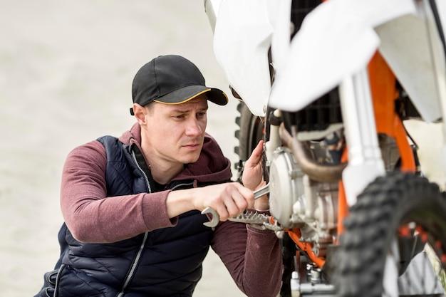 Retrato de hombre tratando de arreglar moto