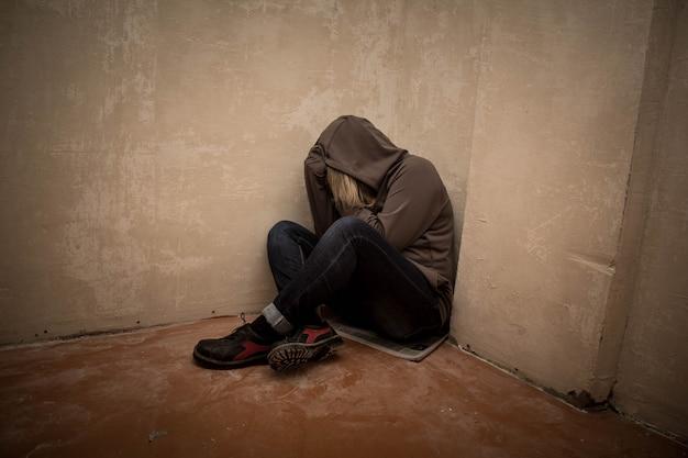 Retrato de hombre triste, drogadicto hombre sentado en el suelo en la esquina