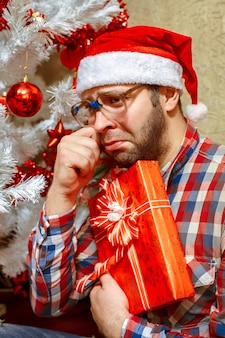 Retrato de hombre triste con regalo de navidad en gorro de papá noel