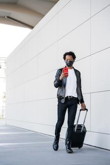 Retrato de hombre turista afro usando su teléfono móvil y llevando maleta mientras camina al aire libre